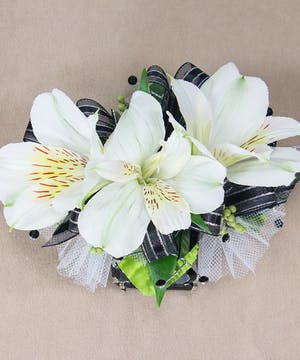 White alstroemeria wristlet with accompanying accent flower and black gem band.