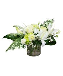 A crisp arrangement of whites and greens designed in a sleek cylinder vase.