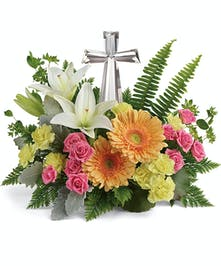 Nestled among bright orange gerberas, pink roses and white lilies, this precious crystal cross keepsake brings joyful reverence to your special occasion.