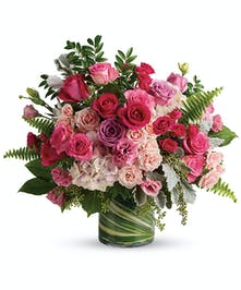 An exquisite fresh flower arrangement of pinks and lavenders designed in a sleek leaf wrapped cylinder vase appropriate for any occasion!