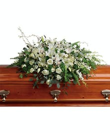 A pure white casket spray that symbolizes peace and beauty.