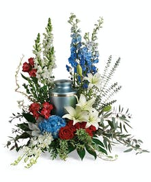 A patriotic red, white and blue sympathy arrangement to display a cremation urn.