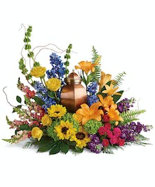 A rainbow of colorful blooms designed to surround a cremation urn.
