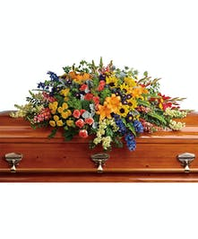 A colorful casket spray full of all the colors in the rainbow.