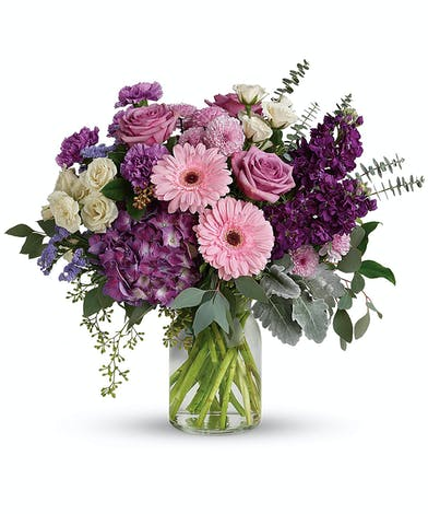 A simply stunning mix of deep purples, lavender and pink designed in a sleek clear vase.