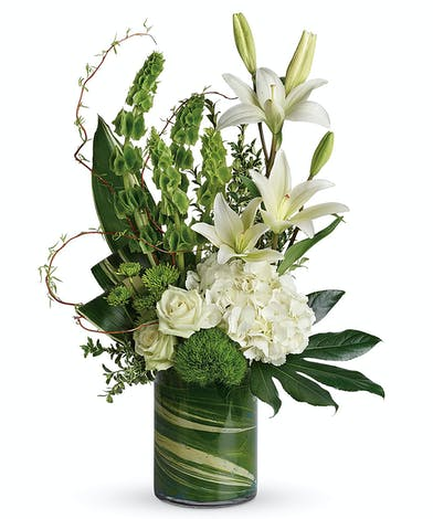 An artistic design of pure white blooms and tropical greens appropriate for any occasion.