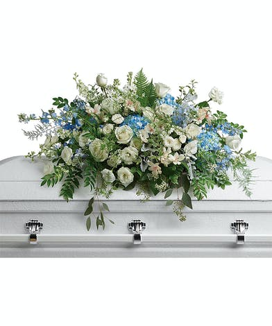 A heavenly casket spray full of pure white and soft blue blooms.