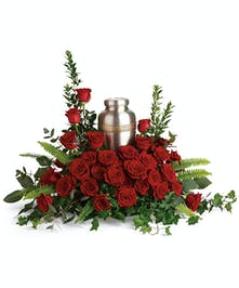 A divine cremation wreath full of rich red roses and delicate greenery.