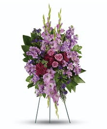 This luxurious standing spray features lavender roses, asltroemeria, gladioli, purple statice and cushions.