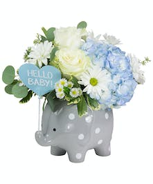 A sweet little baby elephant arrangement with bright blue flowers for a new baby boy.