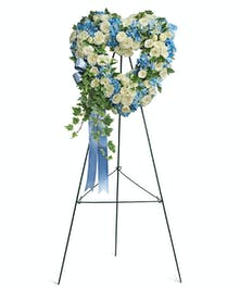 A divine blue and white heart-shaped wreath with sky blue hydrangea and crisp white roses.
