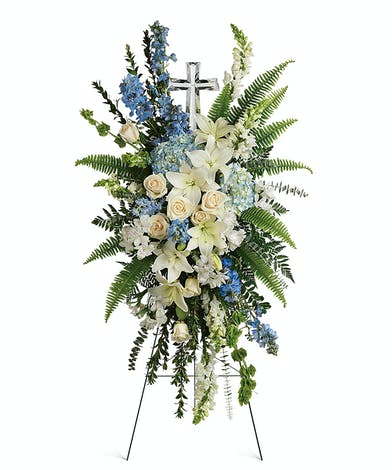A peaceful spray of sof t blues and crisp white accompanied by an ornate crystal cross.