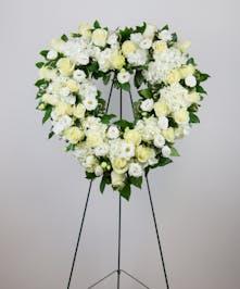 A beautiful open heart standing spray full of crisp white blooms.