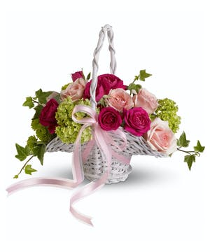 This perfect little basket of pink blooms and fresh greens is trimmed with pink organza ribbon.